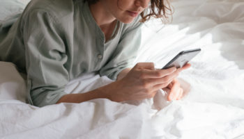 woman-using-smartphone-in-bed-3060643