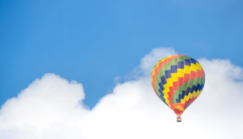 yellow-blue-and-green-hot-air-balloon-flying-near-white-68806
